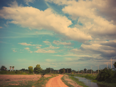 heavy effect: Country dirty road and heavy clouds before raining, Thailand.Vintage filter effect Stock Photo