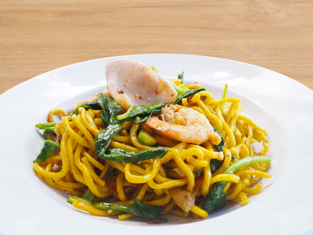 Spicy fried Spaghetti seafood and vegetables on white plate on wood background