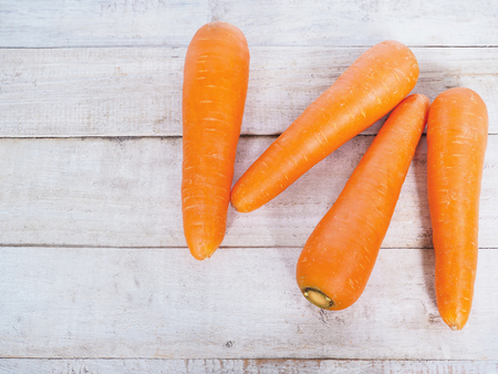 Fresh Organic Carrots on white wooden background