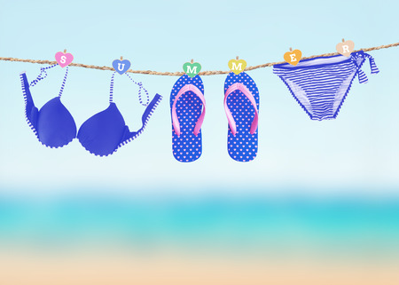 Fashionable woman swimming suit and flip flop hanging on clothesline over blury summer beach background Stock Photo