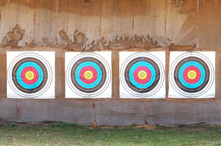 recurve: Row of four archery target rings on old brown fabric background. Stock Photo