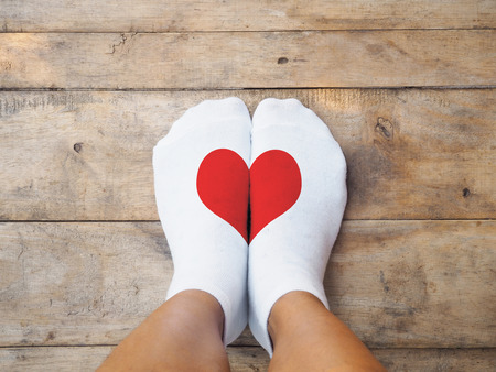 Selfie feet wearing white socks with red heart shape on wooden floor background. Love concept. Фото со стока