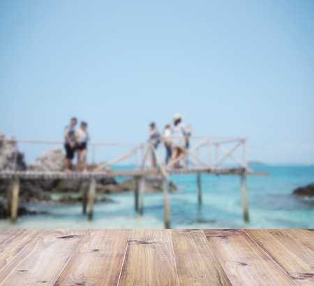 shiny floor: Wooden floor over blurry background of tourists standing on wooden bridge at summer beach.