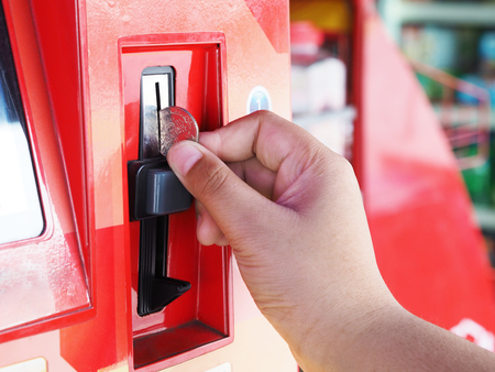 Close-up human hand inserting coin in red telephone vending machine, Thailand. Stock Photo
