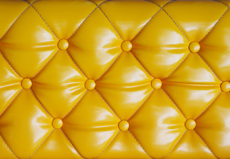 antique furniture: Close up diamond cushion pattern with button of yellow vintage sofa, texture and background