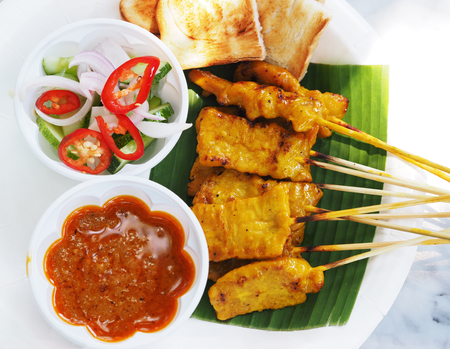 Pork satay, Thai street food, grilled pork served with peanut sauce or sweet and sour sauce on white plate. Stock Photo