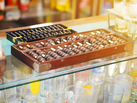calculator chinese: Vintage wooden abacus on glass counter at grocery store