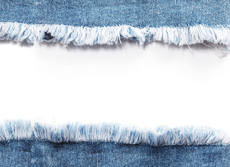Edge frame of blue denim jeans ripped destroyed torn over white background.