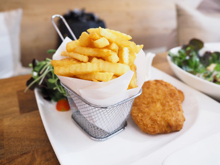 Pile of appetizing french fries served in the metal basket on white plate over wooden table. Stock Photo
