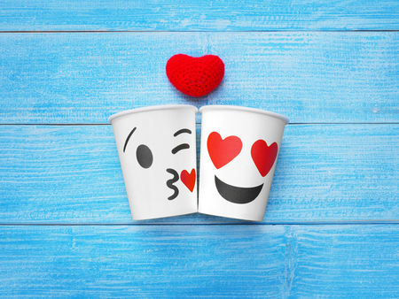 Two white paper cups with face kiss and smile on wood table.