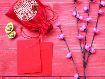 中国の旧正月カードの装飾品。赤い木製の背景に中国の幸運のシンボルと小さなピンクの花の花。松の木に封筒と絹のようなお金の袋。 写真素材