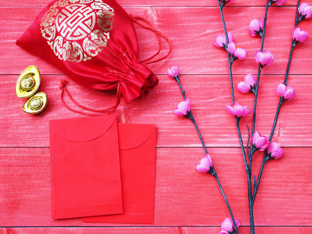 Ornament of Chinese New Year card. China good luck symbol and small pink blossom flower on red wooden background. Envelope and silky money bag on pine wood. Stock Photo