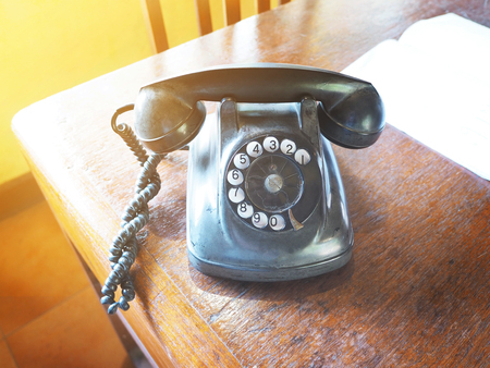 Close up broken vintage dial telephone on wooden brown table, vintage filter effect Stock Photo