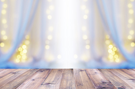Wooden table top over abstract blur background of white curtain with light bulb bokeh at window in bedroom. Banner background with copy space. 版權商用圖片