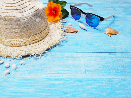 Holiday vacation background.Top view of straw hat, sunglasses, seashells and Chinese rose flower on blue wood with copy space. Banque d'images
