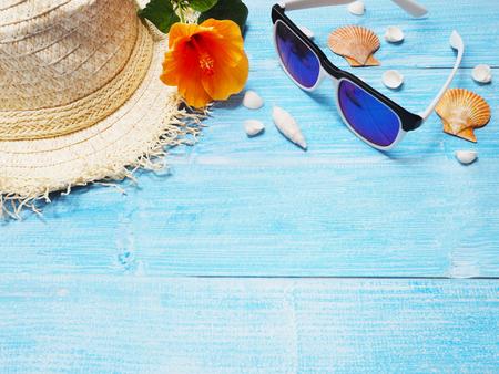 Fond de vacances de vacances Vue de dessus du chapeau de paille, lunettes de soleil, coquillages et fleur rose chinoise sur bois bleu avec espace de copie.
