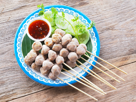Grilled pork meatball and chili spicy sauce with vegatable on white plate over wood table background. 版權商用圖片