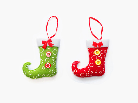 Close up green and red socks with hang ribbon for christmas ornament decoration on white background.