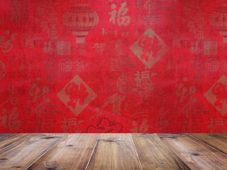 Wood table top over red silk with gold luck symbol pattern. Chinese New Year background. Montage style to display the product.