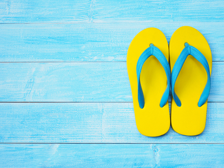 Top view of yellow rubber flip flop shoes on blue wooden background with copy space. Summer holiday vacation concept.