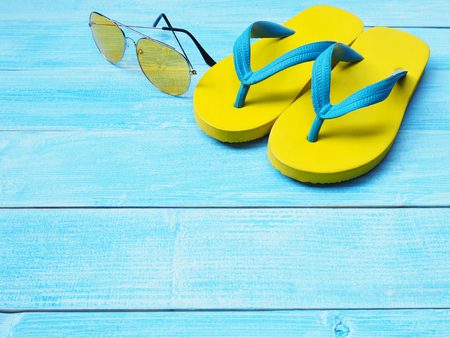 Top view of yellow rubber flip flop shoes and sunglasses on blue wooden background with copy space. Summer holiday vacation concept. 版權商用圖片