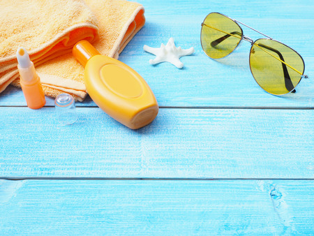 Top view of sunbath accessories or sunblock set on blue wooden background with copy space. Summer holiday vacation concept.