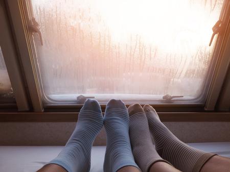 Selfie two human feet in socks stripe pattern on bed nearby window with water drops in the morning.
