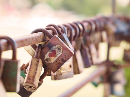 Close up row of rustic padlocks hanging on iron fence.