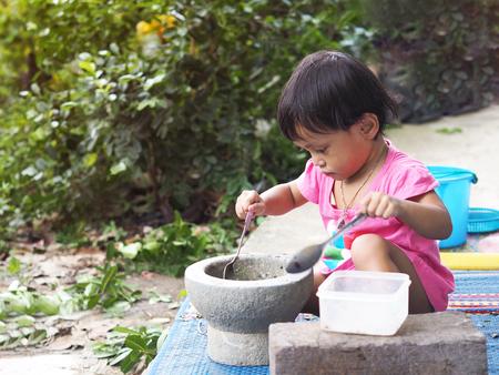 Asian girl kids play cooking papaya salad with mortar in the garden.