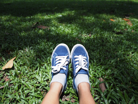 Selfie feet wearing blue sneaker on green grass in the park. Relaxation on springtime background.
