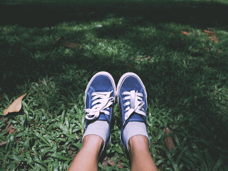 Selfie feet wearing blue sneaker on green grass in the park. Relaxation on springtime background, vintage filter effect.