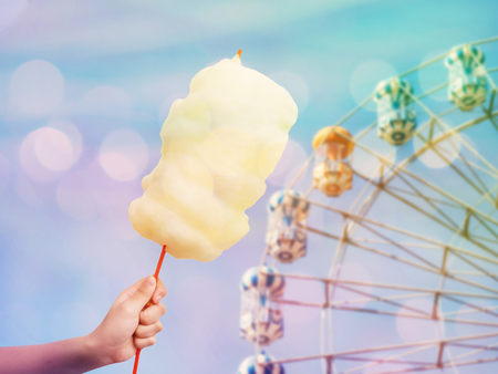 Woman hand holding cotton candy over ferris wheel on blue sky blur background, vintage filter effect. 写真素材