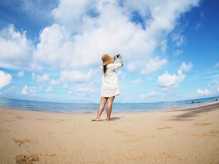 Back view woman taking photograph on the beach. Happy people on summer holiday vacation concept. Fish eye lens distortion