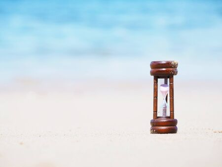 Close up hourglass on summer beach. Sandglass time passing through the bulb as countdown to business deadline concept. Summertime background.