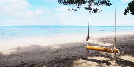 Close up bamboo swing hanging under big tree on the beach. Summer holidays background.