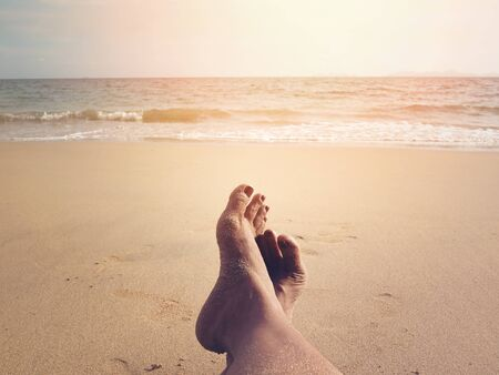 woman selfie barefoot sunbathing on sunset summer beach, vintage filter effect. Happy on holidays vacation concept.