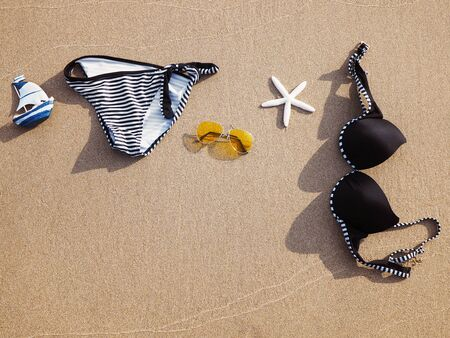 Summer holidays on beach background. Swimsuit and sunglasses on sand at sunset time.