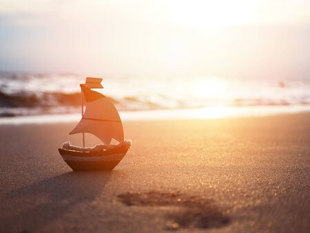 Silhouette small boat toy on sand at sunset with copy space. Vacation on summer beach background concept.