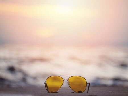 Close up sunglasses with yellow lens on sand at sunset beach. Summer holidays vacation concept. 写真素材