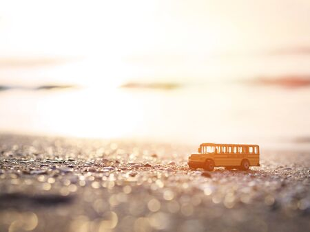 Close up yellow school bus toy on sand at sunset beach background. Summer school holidays concept.