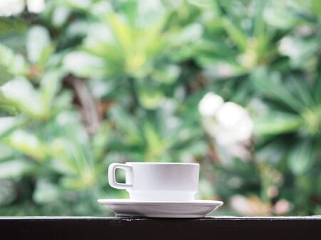 Close up white cup of coffee on wooden table over green floral abstract blur background. 写真素材
