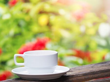 Close up white cup of coffee on wood over red and green floral abstract blur background. 写真素材