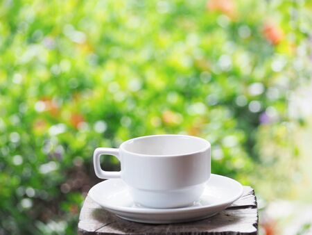 Close up white cup of coffee on wood over green floral abstract blur background. 写真素材