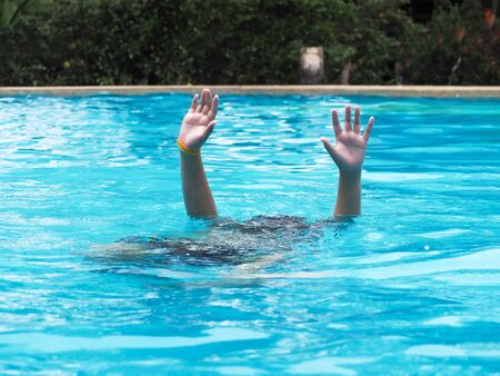 Active Boy diving and raising hands in the air at outdoor swimming pool Kids sinking into the water and need help concept. Stok Fotoğraf