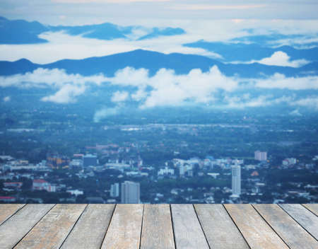 Wood table top over cityscape and mountain with fog from the view point in the morning blur background. Montage style to dispaly the product. Foto de archivo