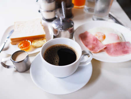 Close up white cup of coffee and breakfast set on white table at restaurant in the morning.