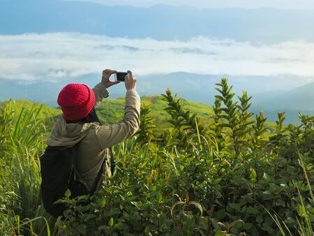 Back viiew of woman tourist backpacker with red hat take photograph by smart phone on the mountain over sunrise fog background.