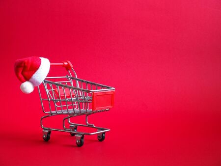 Shopping cart with red Santa Claus hat over red background for Christmas. Online shopping on holidays concept.