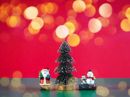 Christmas decorations and traditional ornaments. Small Santa Claus, snowman and pine tree on green color over red background with golden bokeh.