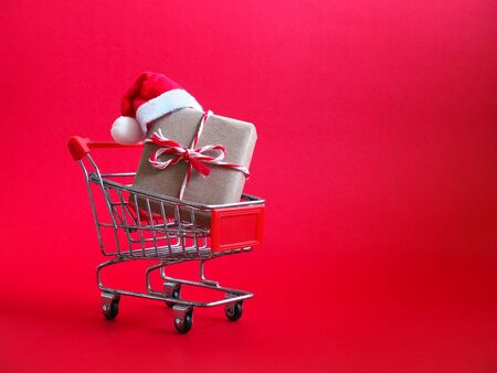 Shopping cart with red Santa Claus hat and Christmas gift over red background. Online shopping on holidays concept. Zdjęcie Seryjne